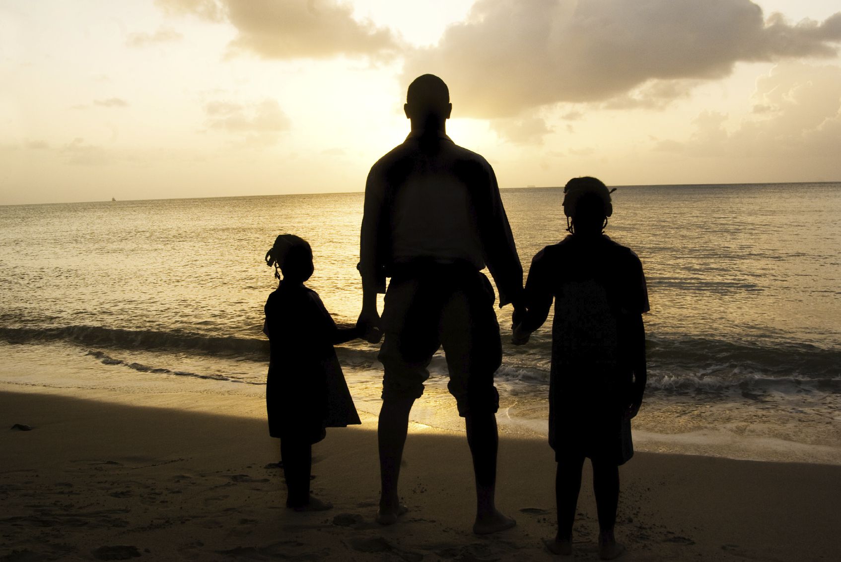father and children silhouette at beach