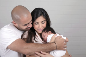 Portrait of happy arabic family at home, young parents holding on hands little sweet newborn baby, love and happiness concept